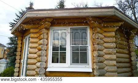Old Wooden Summer House Made Of Beams With Modern Plastic Window In Disrepair From Fairy Tale. Logs