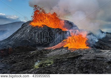 Daytime Volcanic Eruption On Reykjanes Peninsula. Lava Shoots Up From The Crater Above. Crater From