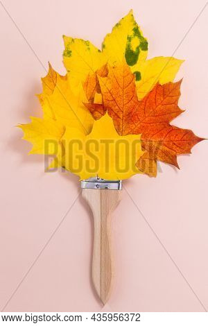 Creative Autumn Concept Made With Paint Brush And Leaves. Paint Brush With Yellow And Red Maple Leav