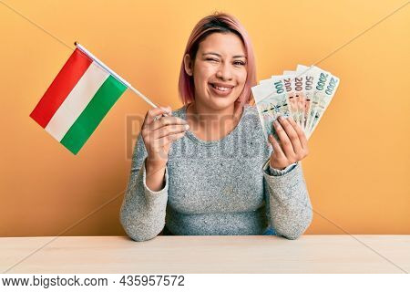 Hispanic woman with pink hair holding czech republic flag and koruna banknotes winking looking at the camera with sexy expression, cheerful and happy face.