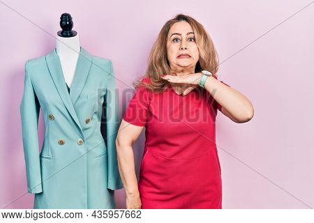 Middle age caucasian woman standing by manikin cutting throat with hand as knife, threaten aggression with furious violence