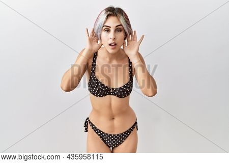Young beautiful woman wearing swimsuit over isolated background trying to hear both hands on ear gesture, curious for gossip. hearing problem, deaf