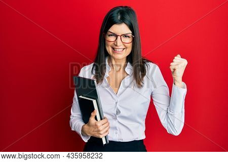 Young hispanic woman wearing business style holding computer laptop screaming proud, celebrating victory and success very excited with raised arm