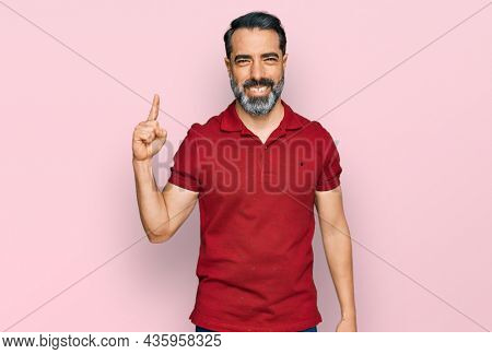 Middle aged man with beard wearing casual red t shirt pointing finger up with successful idea. exited and happy. number one.
