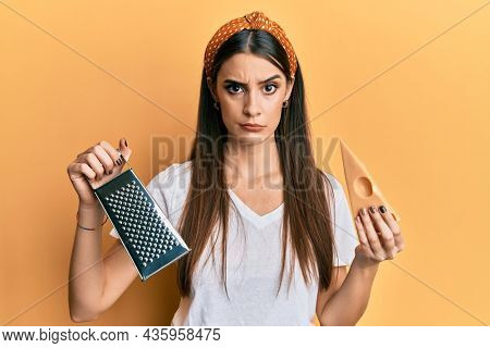 Beautiful brunette young woman holding grater and cheese skeptic and nervous, frowning upset because of problem. negative person.