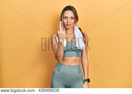 Beautiful hispanic woman wearing sportswear and towel showing middle finger, impolite and rude fuck off expression