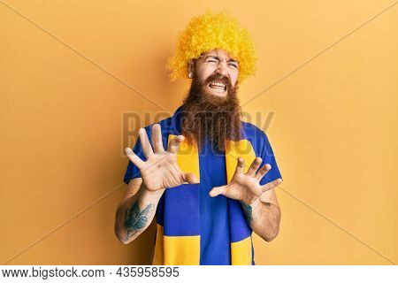 Redhead man with long beard football hooligan cheering game wearing funny wig disgusted expression, displeased and fearful doing disgust face because aversion reaction. with hands raised