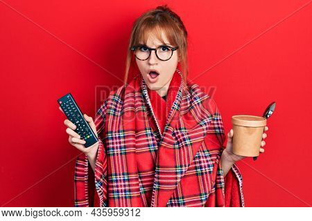 Redhead young woman wrapped in a red warm red blanket eating icecream and watching tv in shock face, looking skeptical and sarcastic, surprised with open mouth