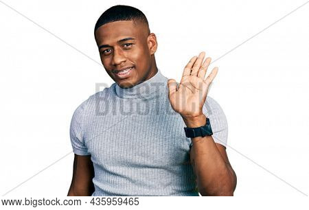 Young black man wearing casual t shirt waiving saying hello happy and smiling, friendly welcome gesture