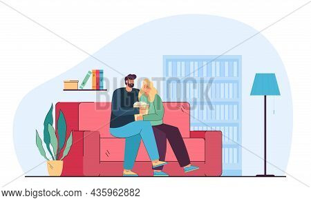 Couple Watching Movie Or Tv Series With Popcorn On Cozy Sofa. Man And Woman Sitting On Couch In Livi
