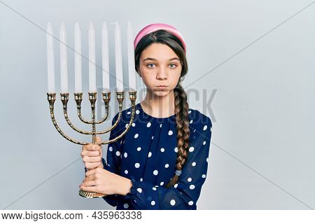 Young brunette girl holding menorah hanukkah jewish candle puffing cheeks with funny face. mouth inflated with air, catching air.