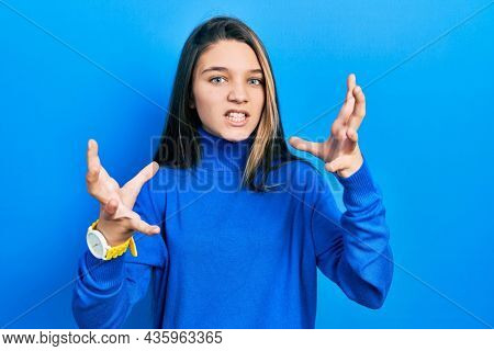 Young brunette girl wearing turtleneck sweater shouting frustrated with rage, hands trying to strangle, yelling mad