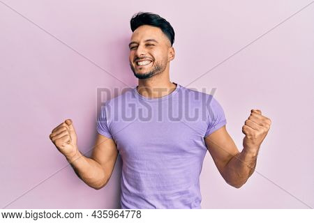 Young arab man wearing casual clothes very happy and excited doing winner gesture with arms raised, smiling and screaming for success. celebration concept.