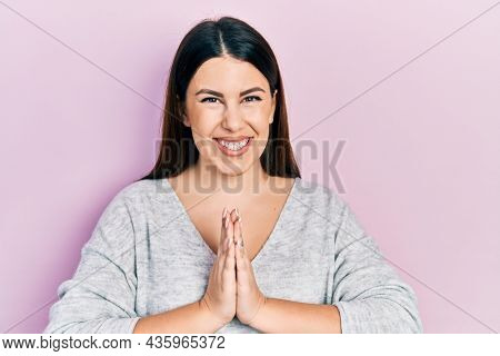 Young hispanic woman wearing casual clothes praying with hands together asking for forgiveness smiling confident.