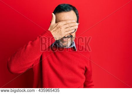 Middle age hispanic man wearing casual clothes and glasses smiling and laughing with hand on face covering eyes for surprise. blind concept.