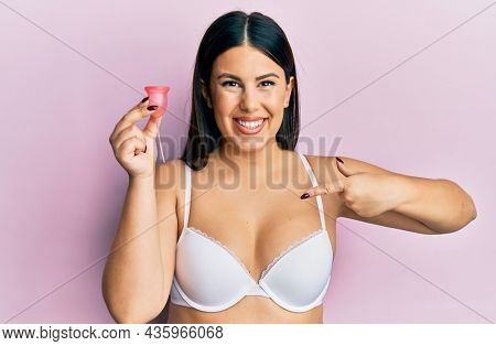 Beautiful brunette woman holding menstrual cup wearing underwear relaxed with serious expression on face. simple and natural looking at the camera.