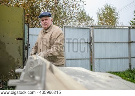 An Elderly Grey-haired Carpenter Cuts A Board On A Machine With A Circular Saw. Selective Focus. A R