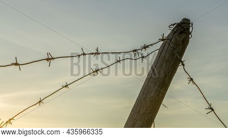 Wooden Anti-tank Barrier From World War Ii. Anti Hedgehog Barbed Wire On Dramatic Sky Background. Sp