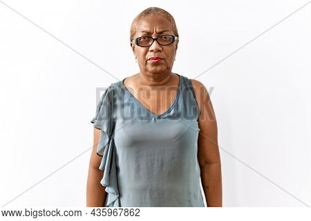Mature hispanic woman wearing glasses standing over isolated background skeptic and nervous, frowning upset because of problem. negative person.