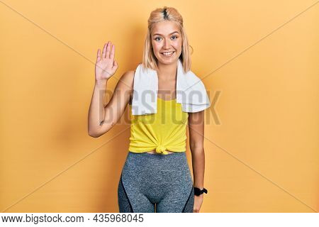 Beautiful blonde sports woman wearing workout outfit waiving saying hello happy and smiling, friendly welcome gesture