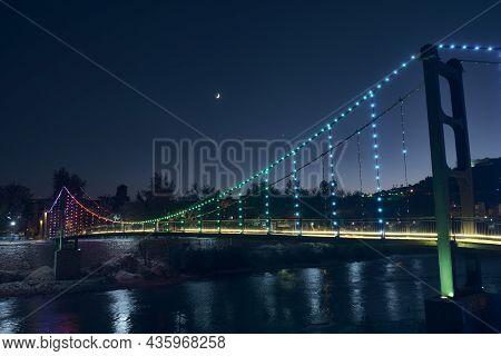Pedestrian Bridge Over River Lightened With Multi-colored Illumination In The Night. Rainbow Colored
