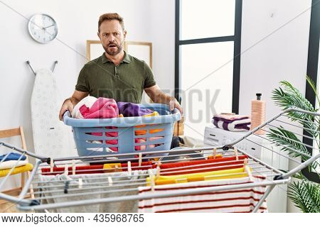Middle age man doing laundry holding basket in shock face, looking skeptical and sarcastic, surprised with open mouth