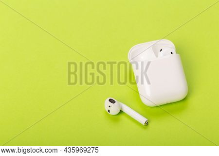 White Wireless Earbuds With Charging Case On Green Background