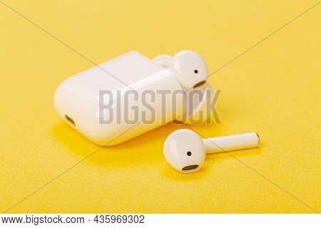 White Wireless Headphones With Charging Case On Yellow Background