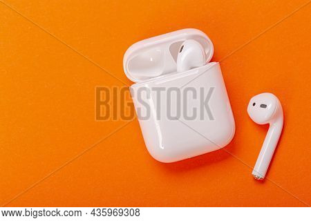 White Wireless Earphones With Charging Case On Bright Orange Background