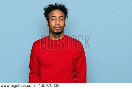 Young african american man with beard wearing casual winter sweater relaxed with serious expression on face. simple and natural looking at the camera.