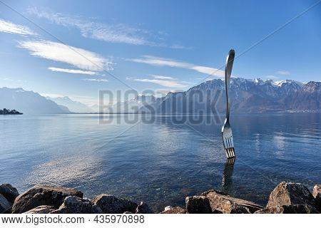 Vevey, Switzerland - Circa 2021: Huge steel fork art installation in Lake Geneva part of the Alimentarium food museum in Vevey, rippling water surface