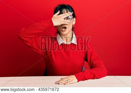 Young brunette woman with bangs wearing glasses sitting on the table peeking in shock covering face and eyes with hand, looking through fingers with embarrassed expression.