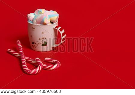 Studio Shot Of A Mug Of Hot Drink With Marshmellows And Candy Canes On Red Colored Background With C