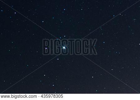 Night, Dark Sky Illuminated By Starlight. Among The Many Stars, One Can See Jupiter Shining Brightly