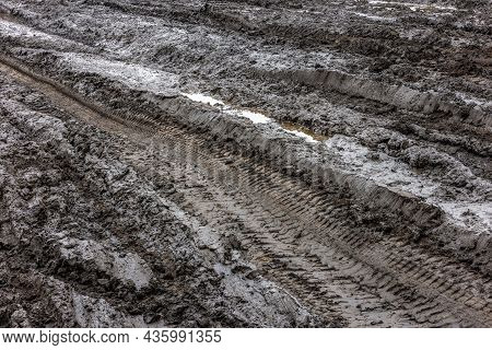 A Broken Rural Country Road. Puddles After Rain On A Dirt Road. Clay, Soil And Puddles At Cloudy Day