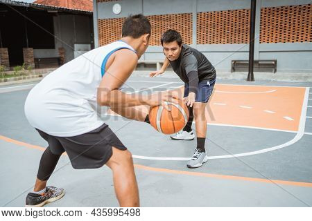 Serious Face Of A Defender Blocking An Opposing Player Dribbling The Ball