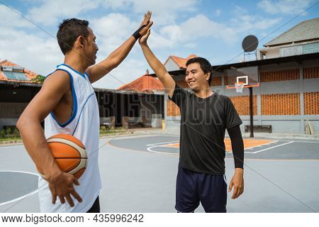 Two Male Basketball Players With High Fives At Break Playing Basketball
