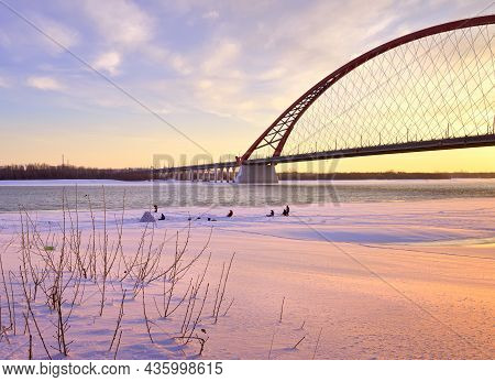 Winter Morning On The Ob. Fishermen On The Ice Of A Frozen River Under The Arch Of The Bugrinsky Aut