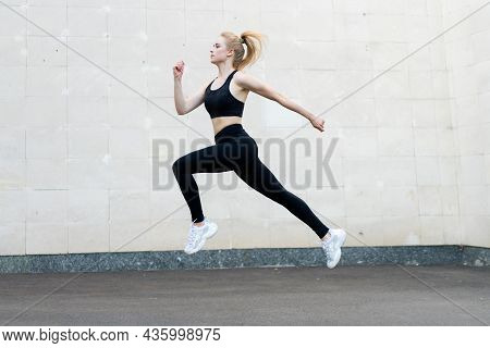 Sport And Fitness Concept Young Adult Caucasian Female Athlete Jumping High Outdoor Gray Tail Wall B