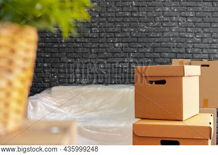 Moving In Or Moving Out Concept. Stack Of Boxes And Packed Furniture