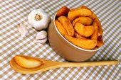 Appetizing village potatoes in bowl on beige tablecloth close-up poster