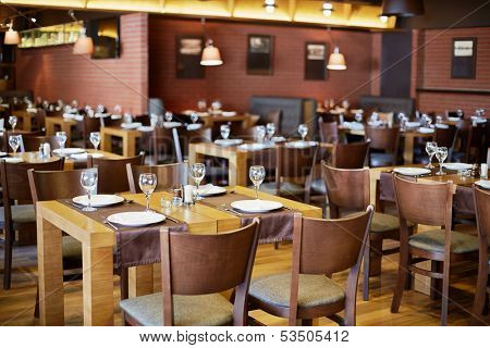 Restaurant roomy hall with wooden furniture and walls of red bricks