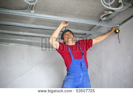 Worker makes a mark on the ceiling profile using a tape measure and pencil