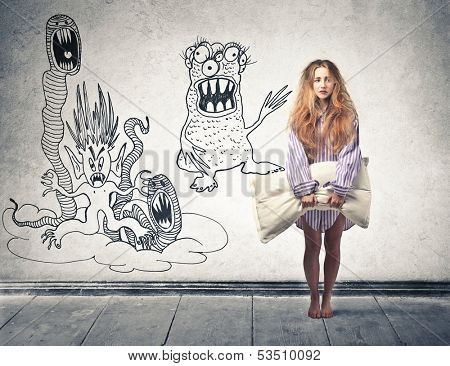 beautiful blonde woman awakened by nightmares with a pillow in hand poster
