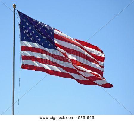 American Flag Flying Against Blue Sky