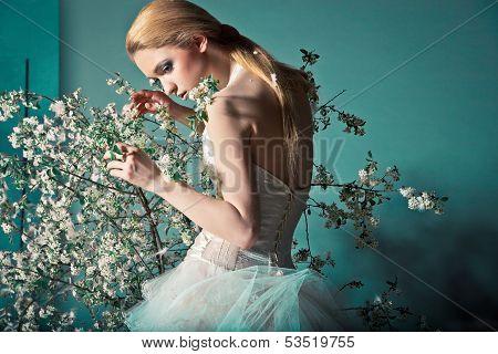 Bride in wedding dress behind bush with flowers