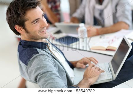 Student in campus relaxing with laptop