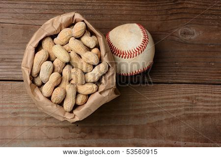 A bag of peanuts and a baseball on an old wooden bench at the ballpark. Horizontal format with copy space.