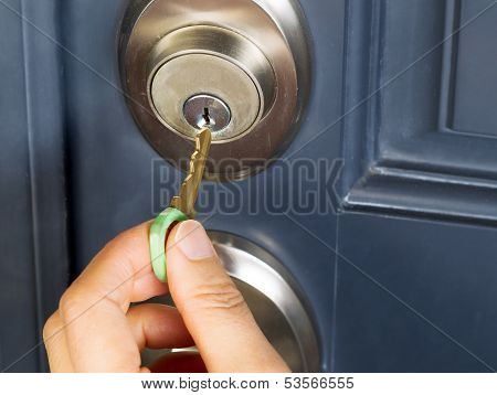Female Hand Putting House Key Into Door Lock