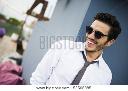 Young business man outdoors, looking casual and relaxed